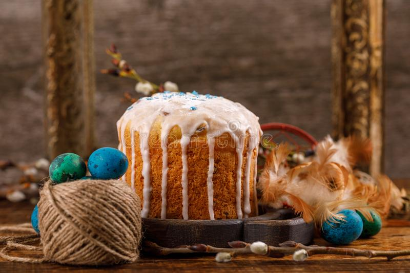 Table with Easter cakes and Easter eggs with willow branches. Easter still life with an ancient frame for a picture in the backgro. Easter still life with an royalty free stock photos