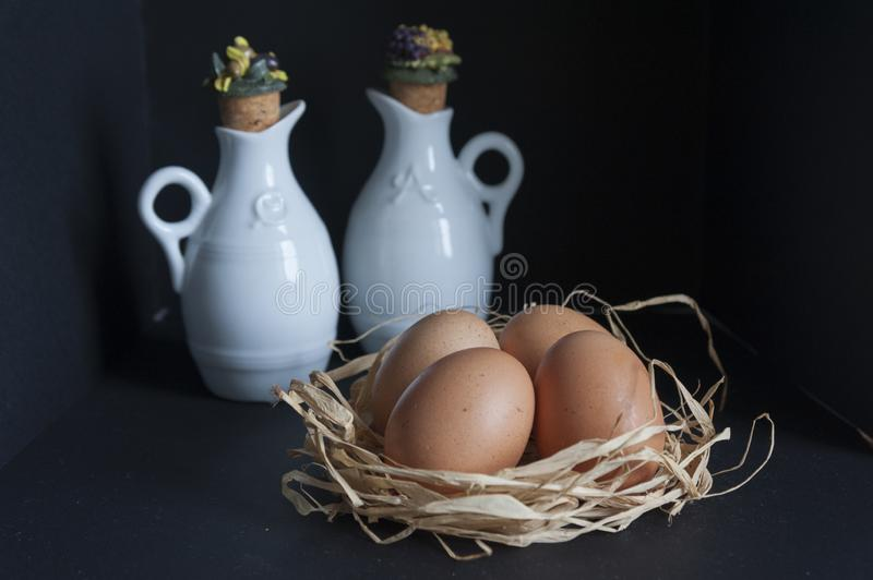 Table with eggs in the straw and oil and vinegar dispenser royalty free stock images