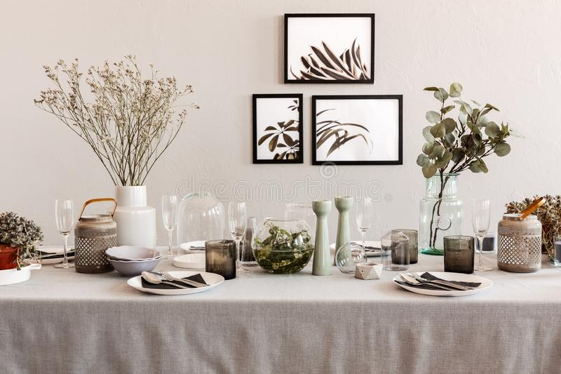 Table with elegant set for dinner, interior with posters on the wall stock image