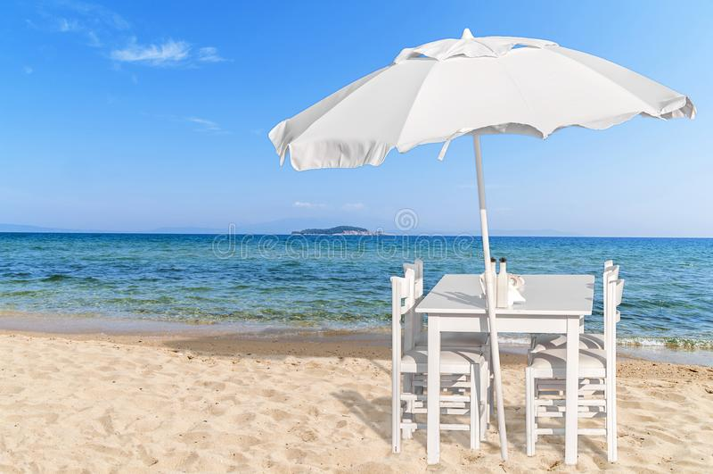Table en bois avec la chaise quatre sur la belle plage sablonneuse et le s bleu images libres de droits