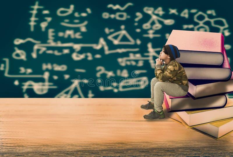Table en bois avec la pile de livre et garçon s'asseyant sur la pile des livres, W images libres de droits