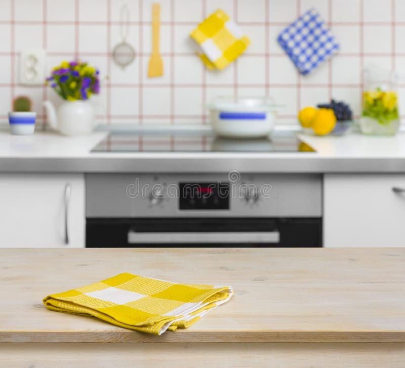 Table en bois avec la serviette jaune sur le fond de cuisine photos libres de droits