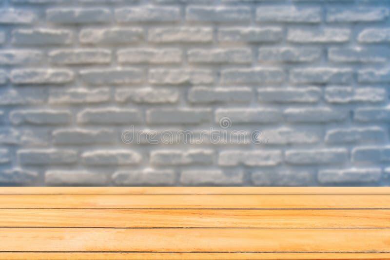 Table en bois avec le fond d'image brouillé du fond grunge blanc rustique de texture de mur de briques photographie stock libre de droits