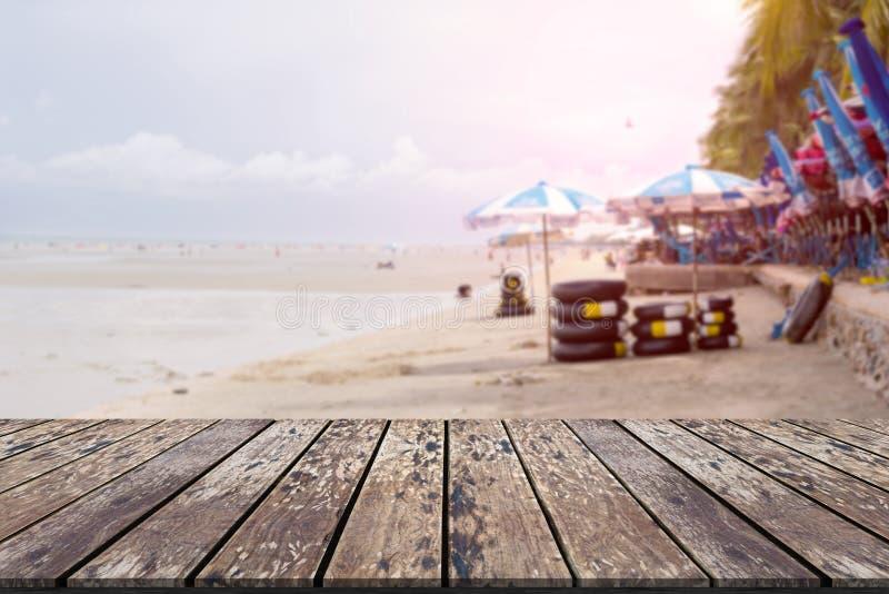 Table en bois avec le fond de tache floue de paysage de plage photo libre de droits