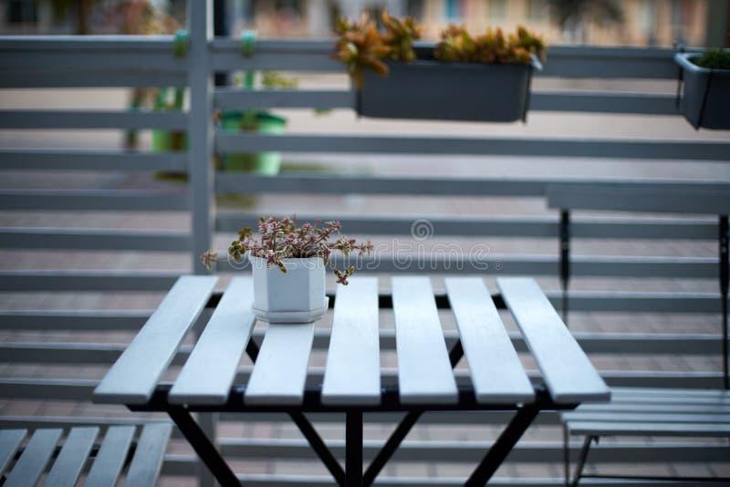 Table en bois blanche de planches, chaises et barrière horizontale de café dans la rue Fond pour le placement de produit D'isolem photos libres de droits