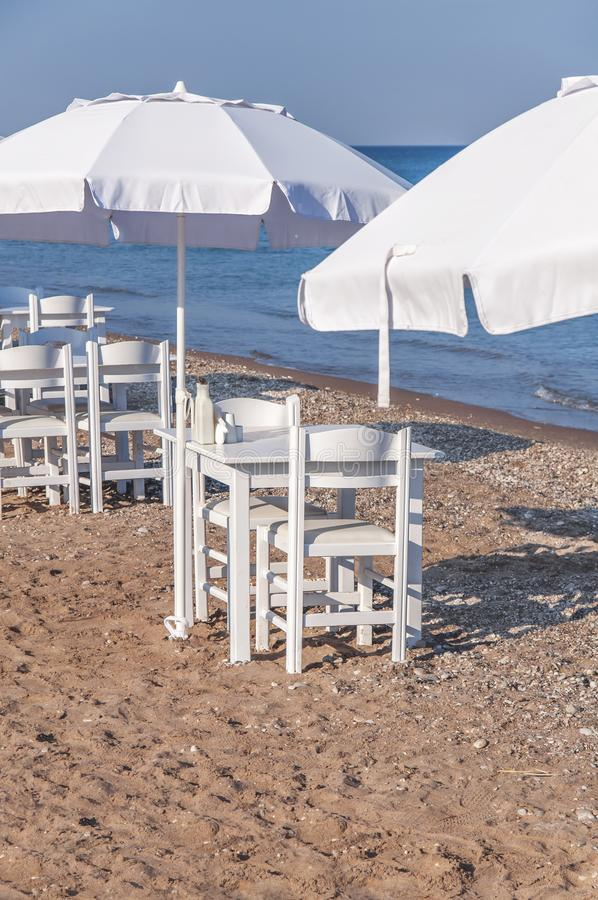 Table en bois blanche sur la plage avec la mer bleue avec la chaise deux images stock