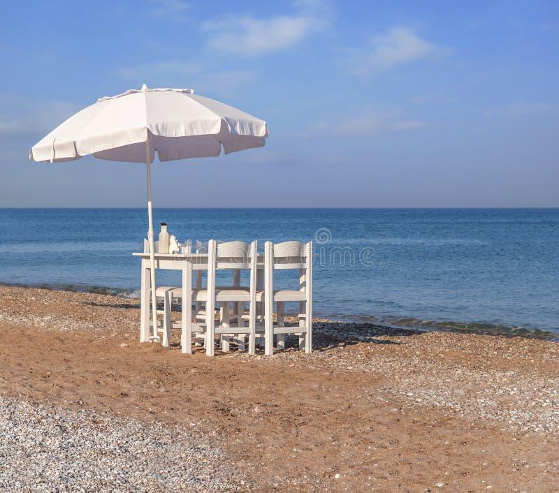 Table en bois blanche sur la plage avec la mer bleue avec la chaise quatre photo stock