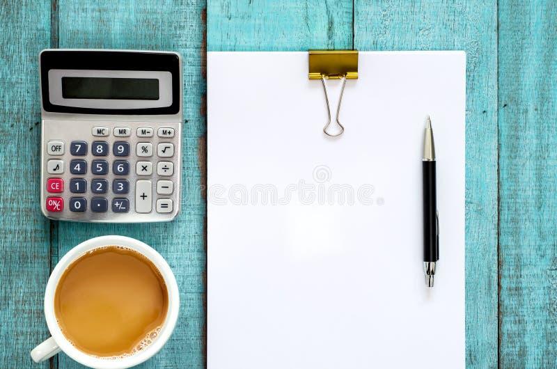 Table en bois bleue de bureau avec la rame de papier, le stylo, la calculatrice et la tasse photographie stock