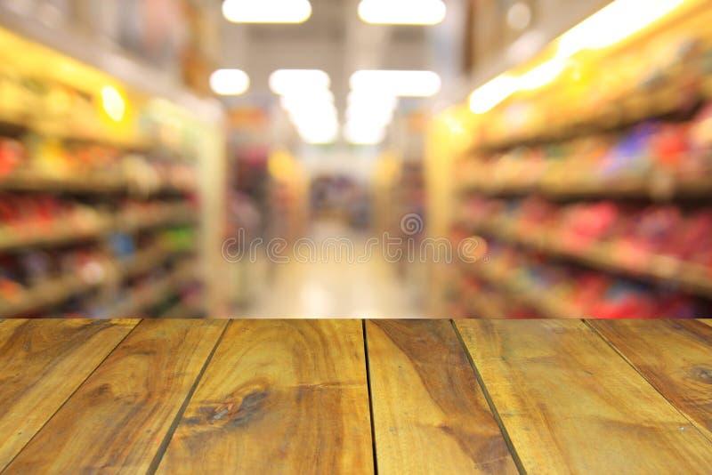 Table en bois brouillée d'image et personnes génériques abstraites de supermarché photographie stock