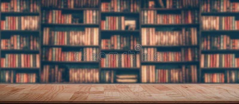 Table en bois dans l'image brouillée beaucoup de vieux livres sur l'étagère dans la bibliothèque photos libres de droits