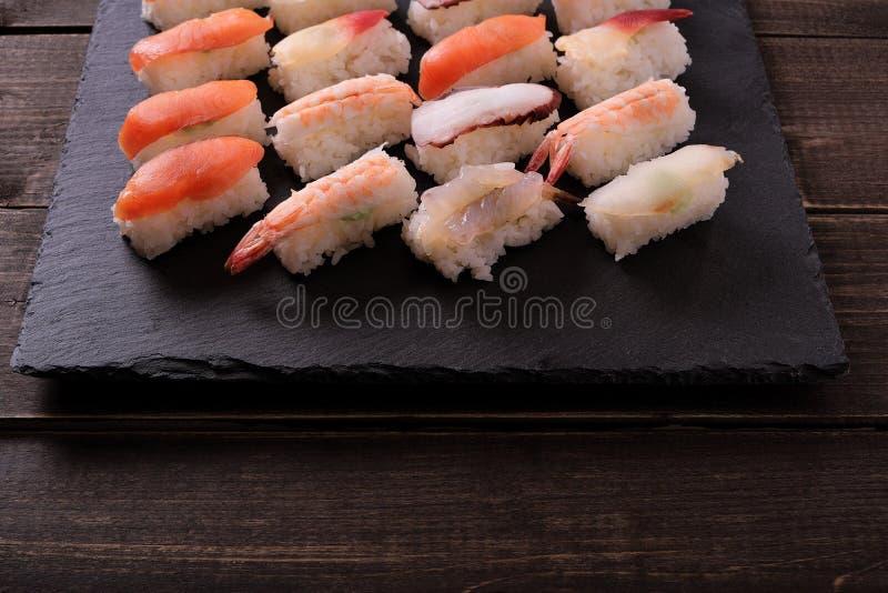 Table en bois de plateau d'ardoise de noir de sélection de nourriture japonaise de sushi diverse image stock