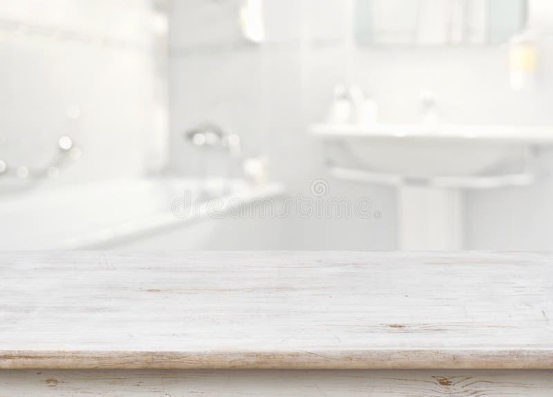 Table en bois devant l'intérieur brouillé de salle de bains comme fond photo stock