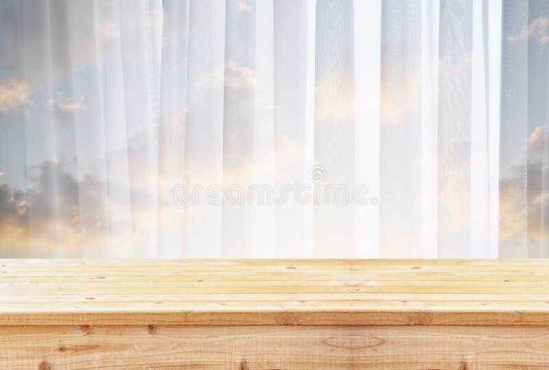 Table en bois devant la lumière brouillée de fenêtre photographie stock libre de droits
