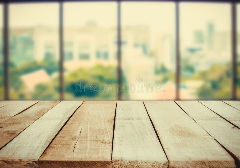 Table en bois devant le fond vert blanc de tache floue abstraite de la fenêtre de bureau photos stock