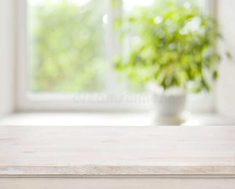 Table en bois légère sur le fond defocuced de fenêtre de ressort photos libres de droits