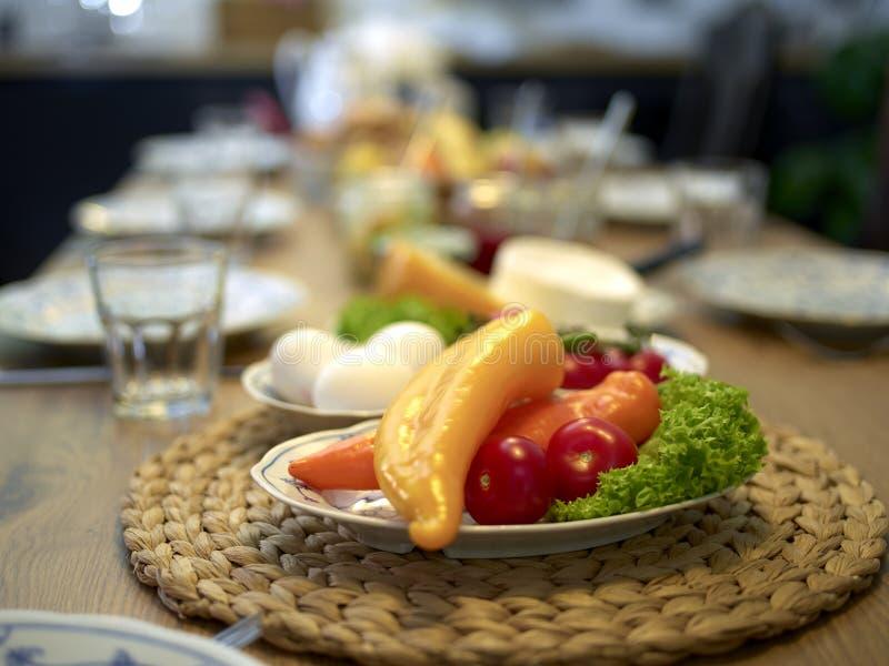 Table en bois mise pour le petit déjeuner concentré sur des paprikas photo stock
