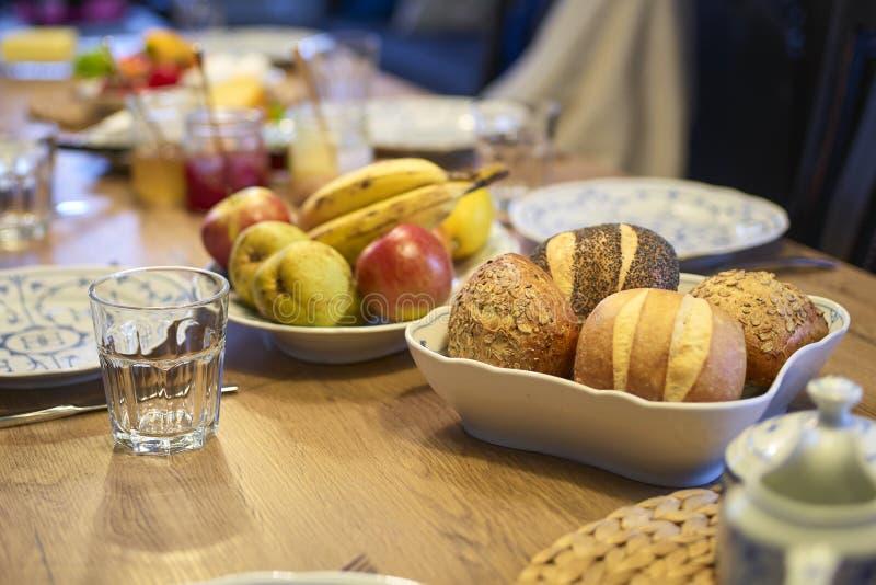 Table en bois mise pour le petit déjeuner concentré sur des petits pains photo libre de droits