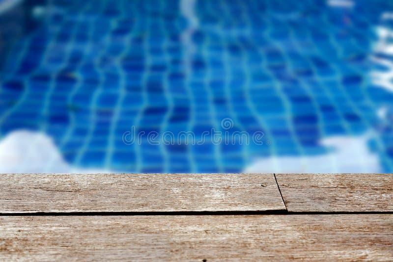 Table en bois rustique vide devant le fond brouillé de la piscine images libres de droits