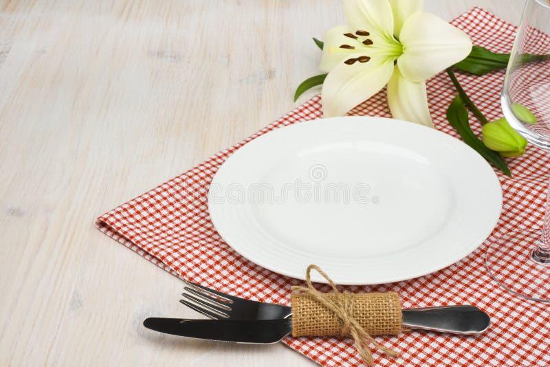 Table en bois servie de restaurant avec des arrangements sur la nappe à carreaux rouge photo stock