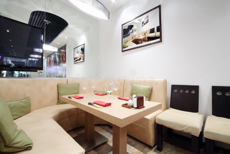 Table en bois, sofa en cuir beige dans le restaurant confortable image libre de droits