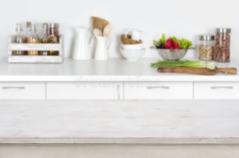 Table en bois sur le fond intérieur brouillé de cuisine avec les légumes frais image libre de droits