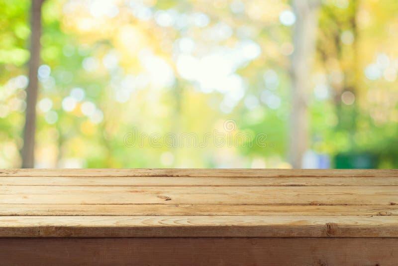 Table en bois vide au-dessus de bokeh de nature d'automne photos stock