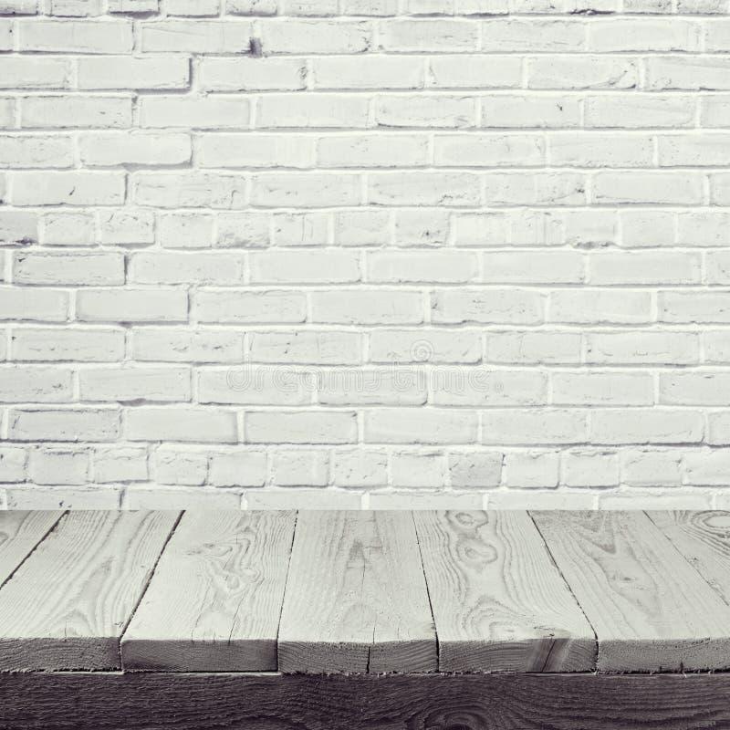 Table en bois vide au-dessus du fond blanc de mur de briques photo stock