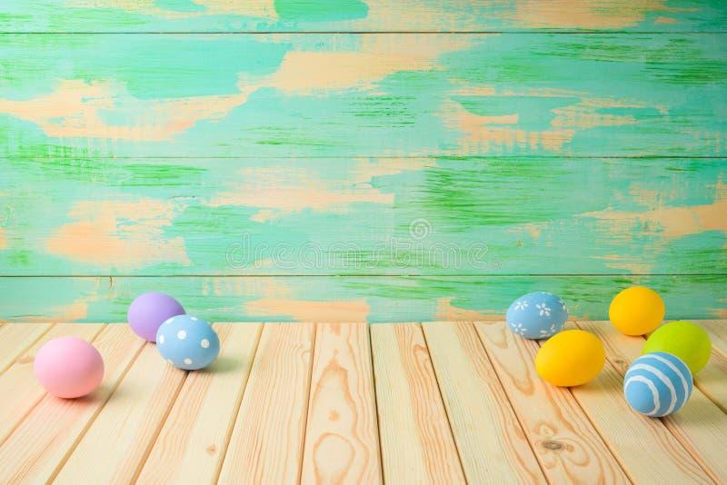 Table en bois vide avec des oeufs de pâques au-dessus de fond coloré photo libre de droits