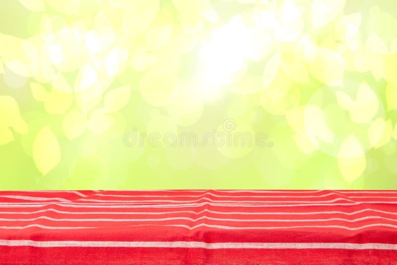Table en bois vide de plate-forme avec la nappe rayée rouge au-dessus du ressort de résumé ou du fond jaune-clair lumineux sensib photographie stock libre de droits