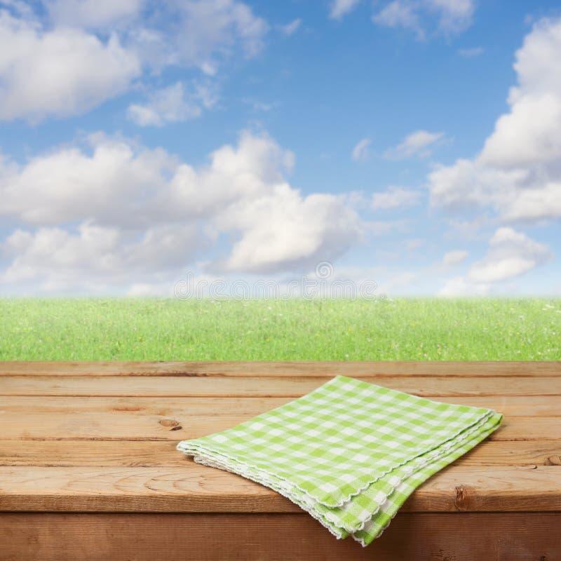 Table en bois vide de plate-forme avec la nappe vérifiée au-dessus du pré d'herbe verte et fond de ciel bleu pour le montage de p images stock