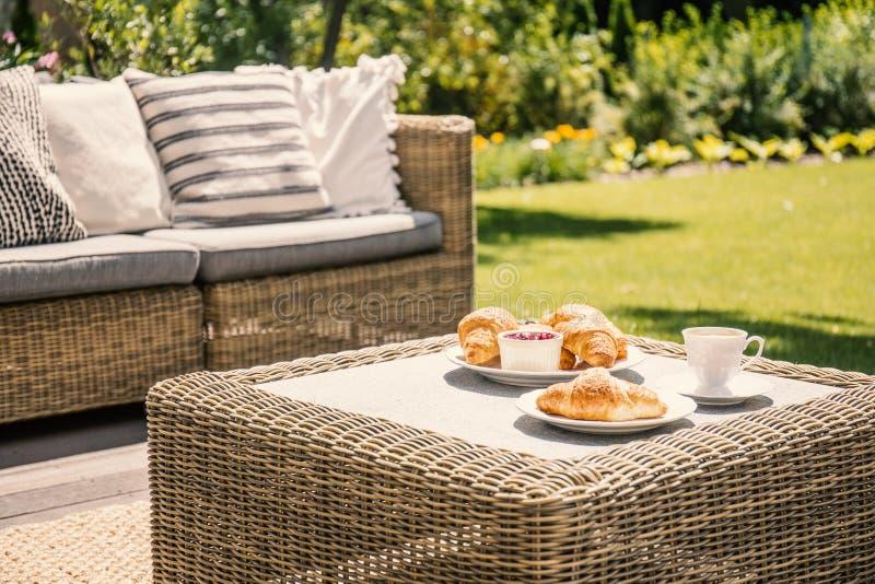Table en osier et canapé de couleur beige sur un porche pendant l'afte ensoleillé images libres de droits