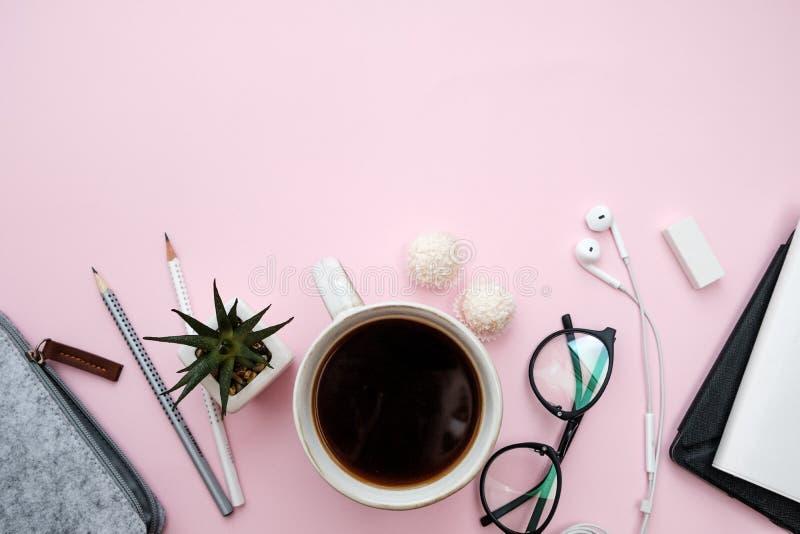 Table en pastel rose avec des accessoires carnet, téléphone, feuille, penci photographie stock libre de droits