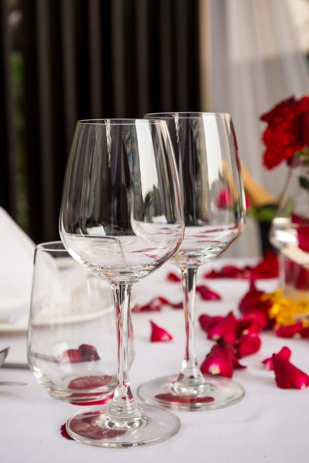 Table en verre de vin mise avec des décorations de pétales de rose photographie stock libre de droits
