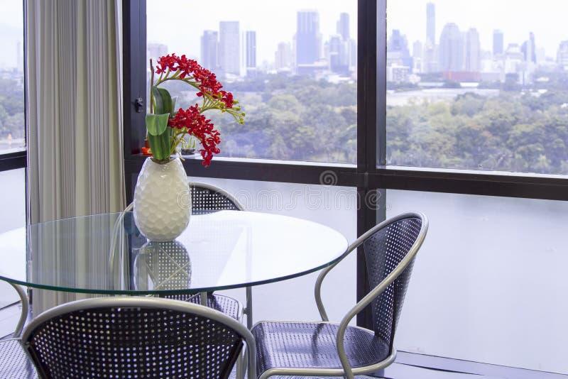 Table en verre ronde avec la chaise noire avec le vase blanc, fleur rouge o photos libres de droits