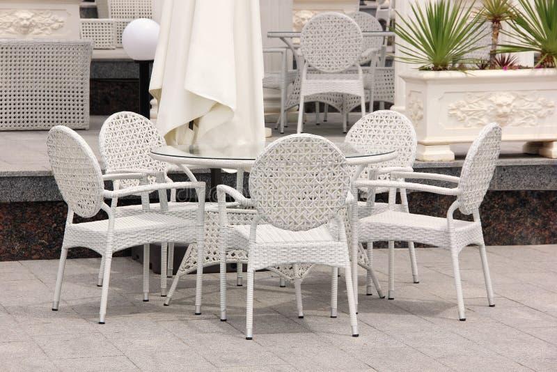 Table et chaises en osier blanches dans le café de rue photos stock