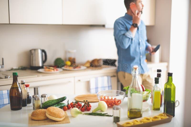 Table et homme de cuisine parlant sur le téléphone portable sur le fond brouillé photos stock