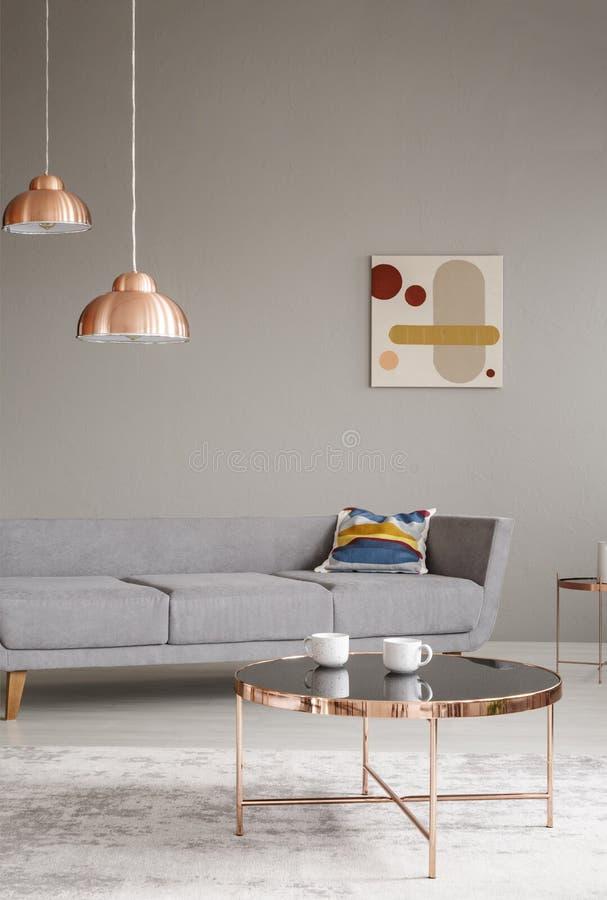 Table et lampes de cuivre dans un intérieur gris de salon Photo réelle photos stock