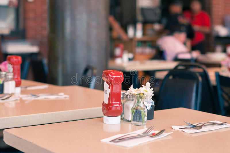 A Table in a Fast Food Cafe Served with a Ketchup Bottle. A bottle of ketchup is serving on the table in a classical american diner stock photography