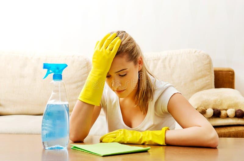 Table fatiguée de nettoyage de jeune femme dans les gants jaunes photos stock