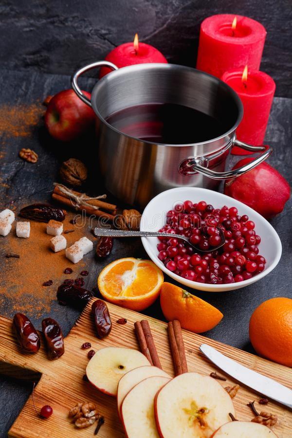 On the table is mulled wine, plate with cranberries, a board with apples, cinnamon and dates and next burning candles. On the table is a fragrant mulled wine in stock photos