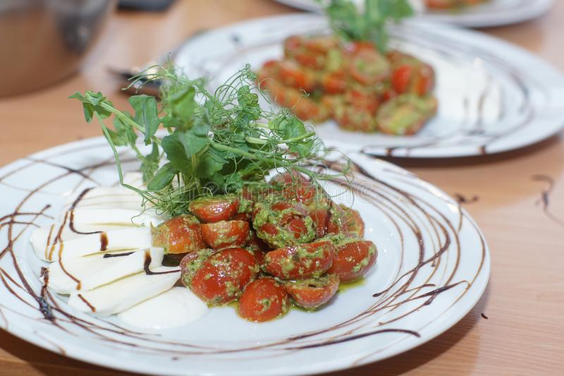 On the table is a freshly prepared caprese salad with pesto and cherry tomatoes for several people stock photography