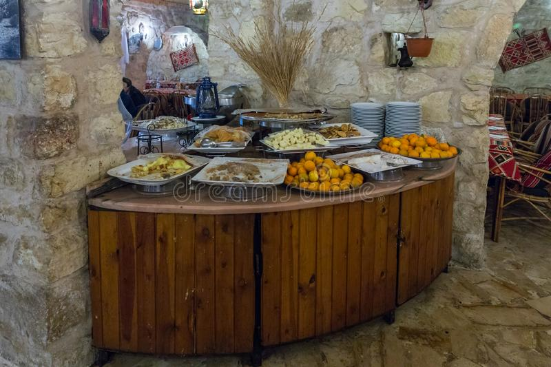 A table with fruit and sweet snacks stands in a corner in a roadside restaurant near the city of Wadi Musa in Jordan. Wadi Musa, Jordan, December 06, 2018 : A royalty free stock images