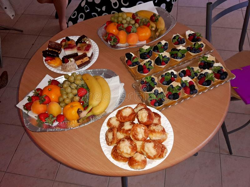Table full of food and snacks such as fruit, cookies and sweets. Image stock photos