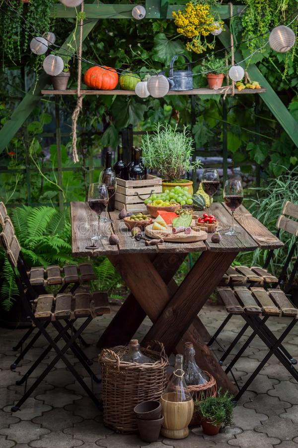 Table full of snacks and wine in the evening. On old wooden table stock photography