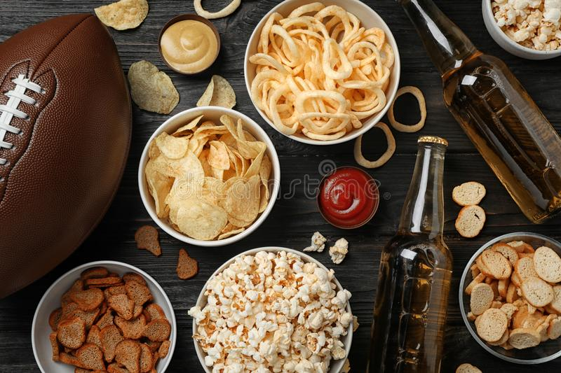 Tasty snacks and beer prepared for watching American football on table royalty free stock photos