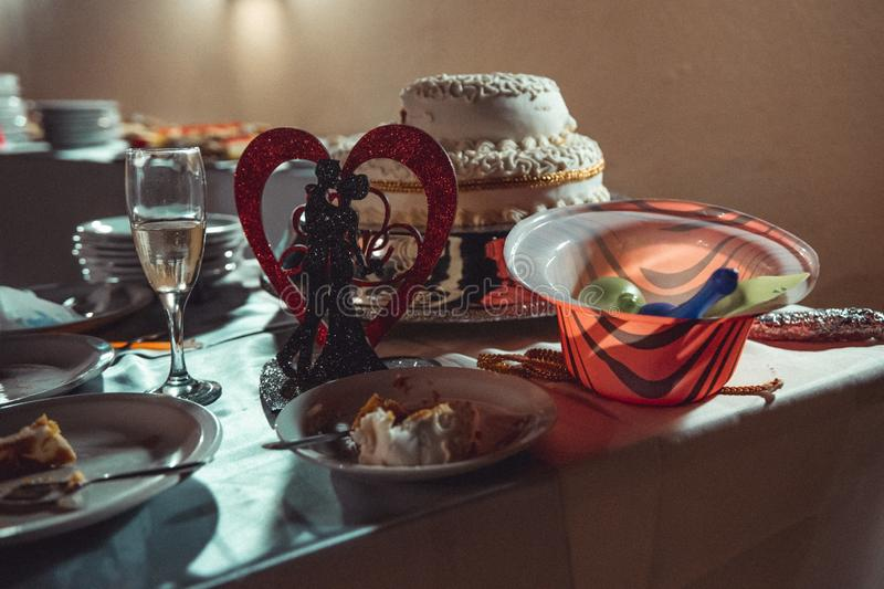 Table full of wedding ceremony cake leftovers and decorations royalty free stock images