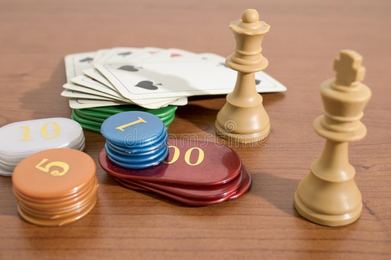 Table games cards, chess and casino chips on a wood table. Composition royalty free stock photo