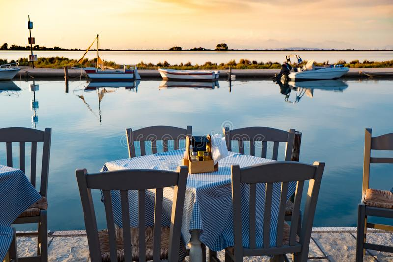 Table grecque traditionnelle de taverne près de la mer au coucher du soleil images stock