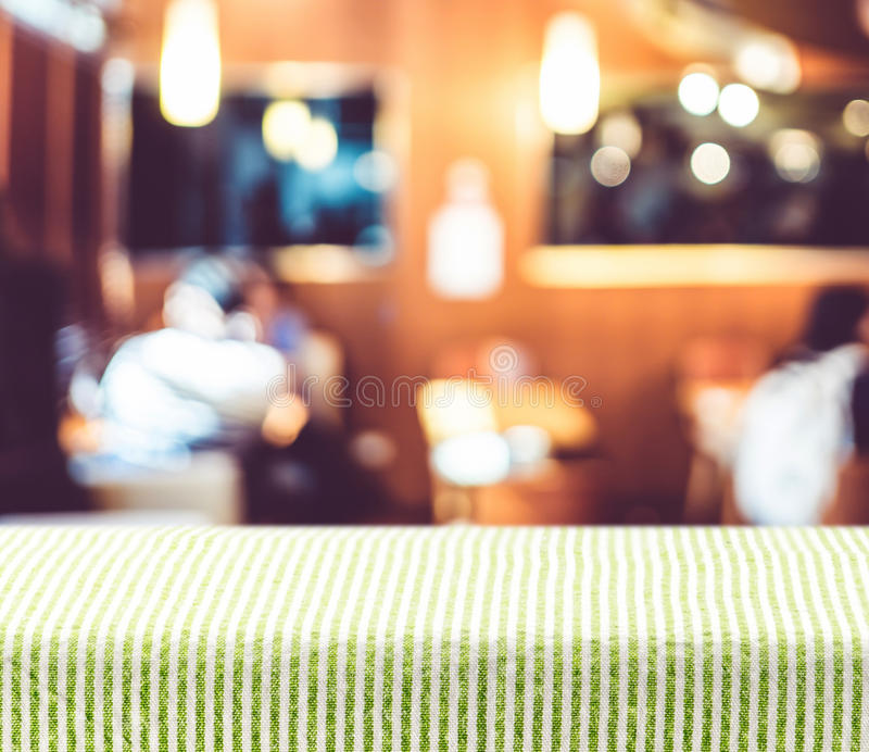Table with green pattern tablecloth with blur restaurant background,Mock up for display of product.  stock photography