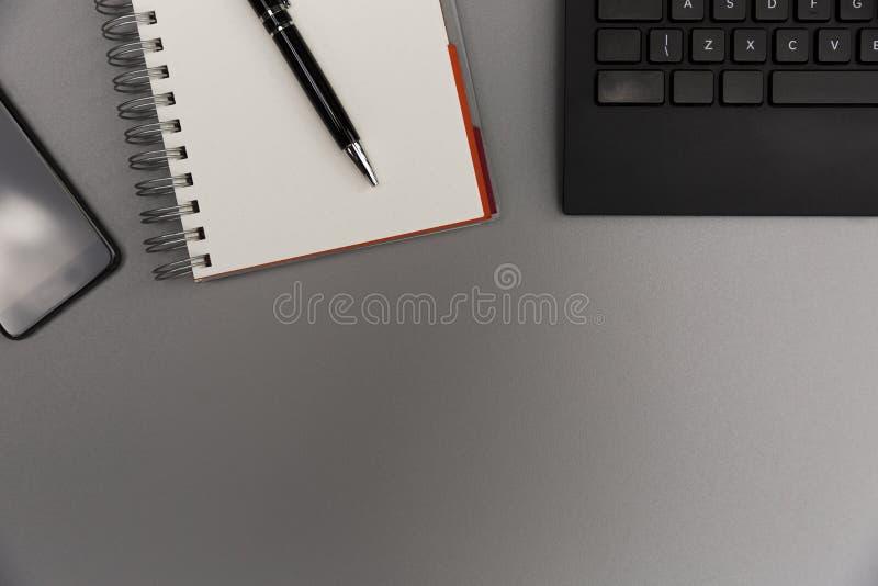 Table grise moderne de bureau avec le smartphone, PA vide de carnet image libre de droits